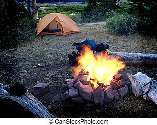 Campfire with tent in background for camping scene