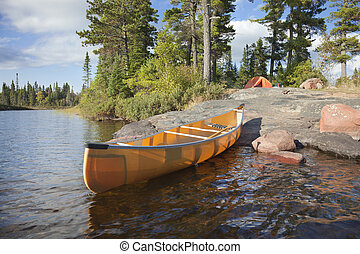 Campsite and canoe on rocky shore of lake