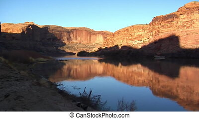 campsite and Colorado River, red rock cliffs at sunset