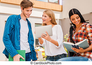 Campus life is awesome! Smiling young woman showing something on digital tablet to young man while young woman reading a book