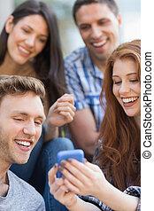 campus, studenci, smartphone, patrząc, zewnątrz, szczęśliwy