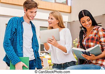 campus, vida, é, awesome!, sorrindo, mulher jovem, mostrando, algo, ligado, tablete digital, para, homem jovem, enquanto, mulher jovem, lendo um livro