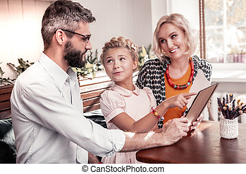 Nice young girl pointing at one position on the menu