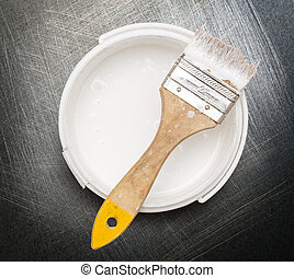 Can of white paint with brush