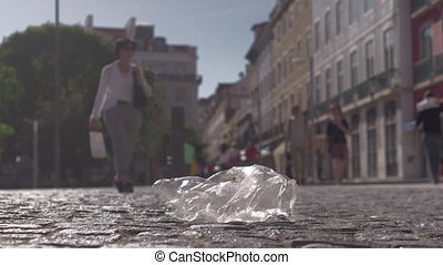 A transparent plastic packet, being moved by wind on a city pavement