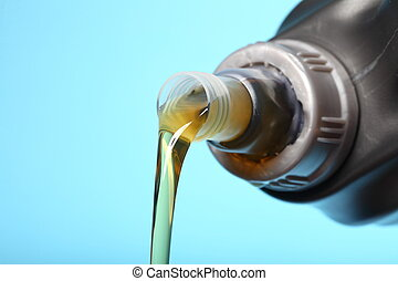 Can with car engine oil pouring in front blue background