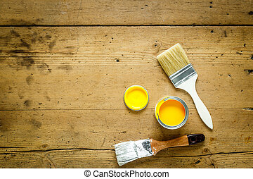 Can with yellow paint and brush on wooden background