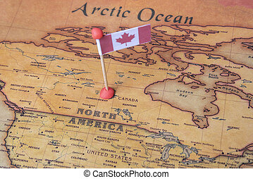 Canada is marked with a flag on the map. Flag of Canada on the world map.
