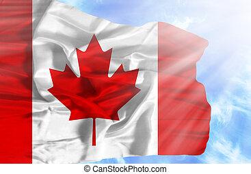 Canada waving flag against blue sky with sunrays