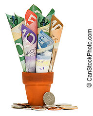 Canadian cash and coins - Canadian bills rolled up in a...