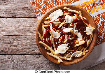 Canadian cuisine: poutine with sauce and cheese. horizontal...