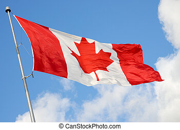 Canadian Flag Against Blue Sky - Canadian Flag Blowing in...
