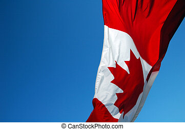 Canadian flag blowing in the wind on a clear day.
