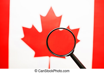 Canadian flag looking through a magnifying glass. A study of the history and culture of the people of Canada. The concept of studying geography, customs