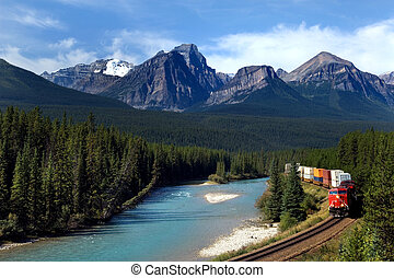Freight train moving along Bow river in Canadian Rockies
