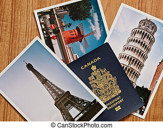 Canadian passport with selection of European travel photos on wooden table