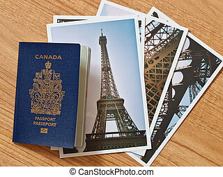 Canadian passport with selection of Parisian travel photos on wooden table