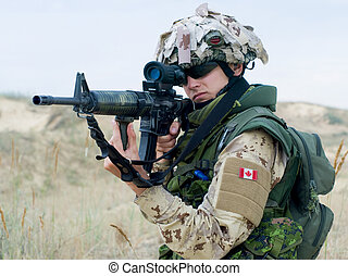 canadian soldier - soldier in desert uniform aiming his...