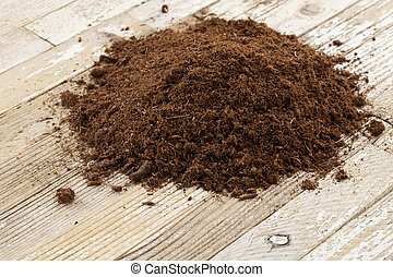 Canadian sphagnum peat moss used as soil conditioner in gardening, a small pile on a grunge wooden surface
