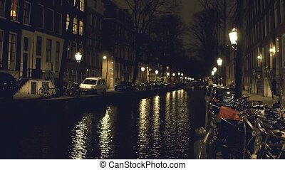 Canal and houses on embankments in Amsterdam at night