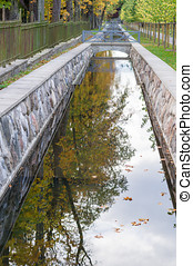 Canal closeup with autumn tree reflection in water