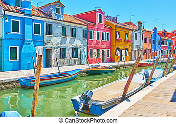 Perspective of canal with boats and picturesque houses in Burano ,  Venice, Italy
