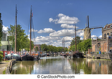 Canal in Gouda, Holland - Windmill and historical boats in a...
