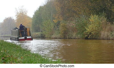 Canal passenger boat in autumn - Man is driving a narrow...