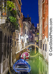 canal with boats and old buildings at night. Venice city, Italy