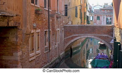 Canal with bridge and moored boats in Venice - Perspective...