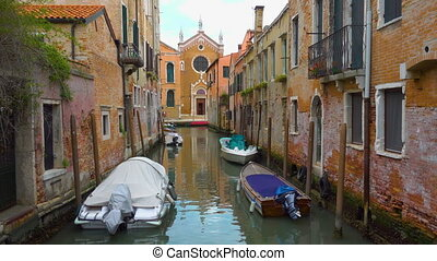 Canal with church in the end and moored boats in Venice -...