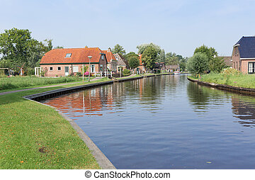 Canal with houses in rural landscape near Giethoorn, the Netherlands