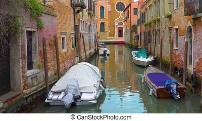 Canal with moored boats in Venice - Perspective of small...