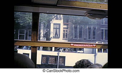 Sea view of Amsterdam homes architecture and street by boat tour in Holland. Historical archival Amsterdam touristic cruise in the capital city of Netherlands in the 1970s.