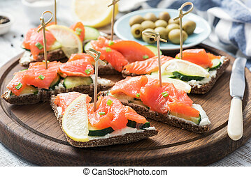Canape sandwiches with salmon, cucumber and cream cheese
