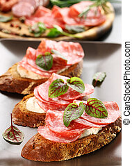 Canape with cream cheese, salami and herbs