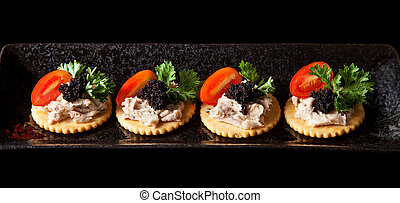 Canape made from biscuit, tuna pate, tomato, pasley and...