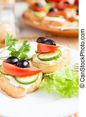 Canape with soft cheese and olives, close up food