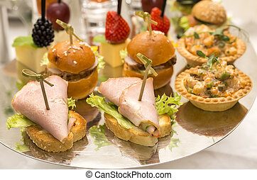 Canapes of cheese vegetables meat and seafood on white...