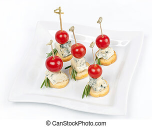 Canapes on a plate with cheese and cherry tomatoes