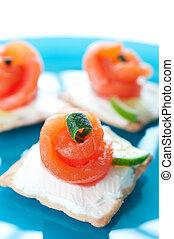 Canapes with smoked salmon on blue plate