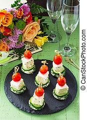Canap?s with white bread, cucumber, feta cheese and cherry tomatoes on a festive table. Valentine's Day or wedding.