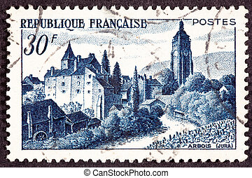 Canceled French Postage Stamp showing the Chateau Bontemps, in Arbois, Jura, France. In the foreground is a vinyard