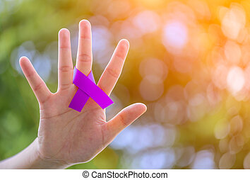 Cancer Awareness campaign. Female hands holding Purple CANCER awareness ribbon on green bokeh background..