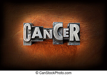 The word cancer made from vintage lead letterpress type on a leather background.
