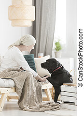 Cancer woman interacting with dog
