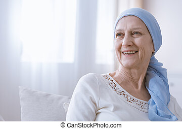 Happy woman with cancer in blue headscarf smiling with hope