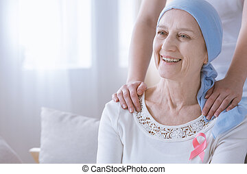 Cancer woman wearing pink ribbon - Smiling woman with cancer...
