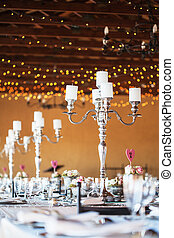 Candelabra with candles on decorated wedding reception...