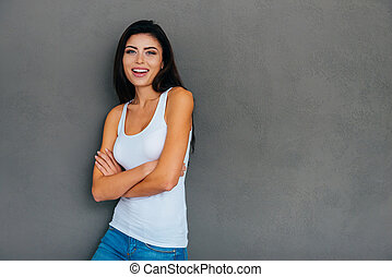 Candid beauty. Beautiful young woman in white tank top keeping arms crossed and smiling while standing against grey background